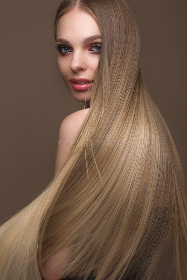 Härlig blond flicka med ett perfekt slätt hår, klassiskt smink Härlig le flicka royaltyfria foton