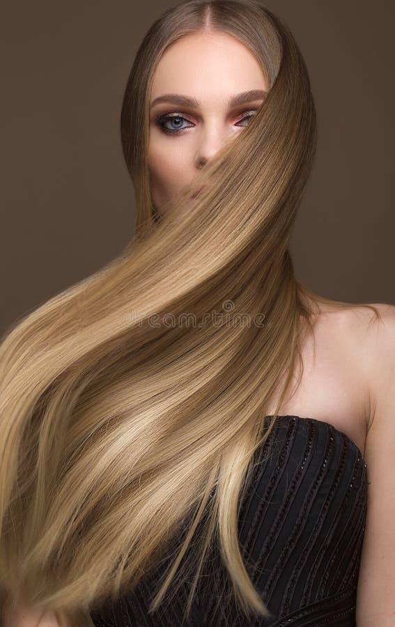 Härlig blond flicka med ett perfekt slätt hår, klassiskt smink Härlig le flicka arkivfoton