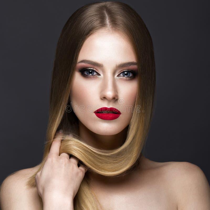 Härlig blond flicka med ett perfekt slätt hår, ett klassiskt smink och röda kanter Härlig le flicka arkivbild