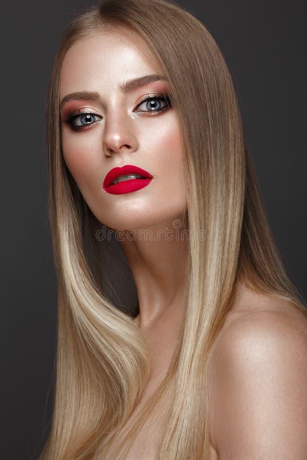 Härlig blond flicka med ett perfekt slätt hår, ett klassiskt smink och röda kanter Härlig le flicka royaltyfria foton