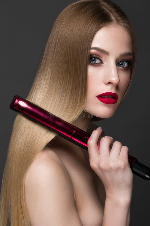 Härlig blond flicka med ett perfekt slätt hår, krulla, ett klassiskt smink och röda kanter Härlig le flicka fotografering för bildbyråer