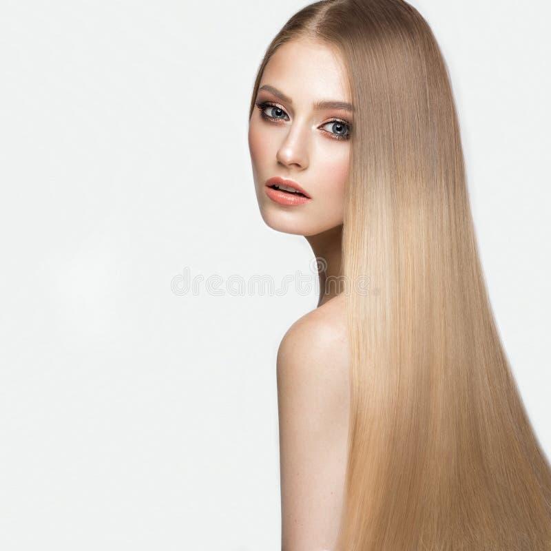 Härlig blond flicka med ett perfekt slätt hår och klassiskt smink Härlig le flicka royaltyfri fotografi