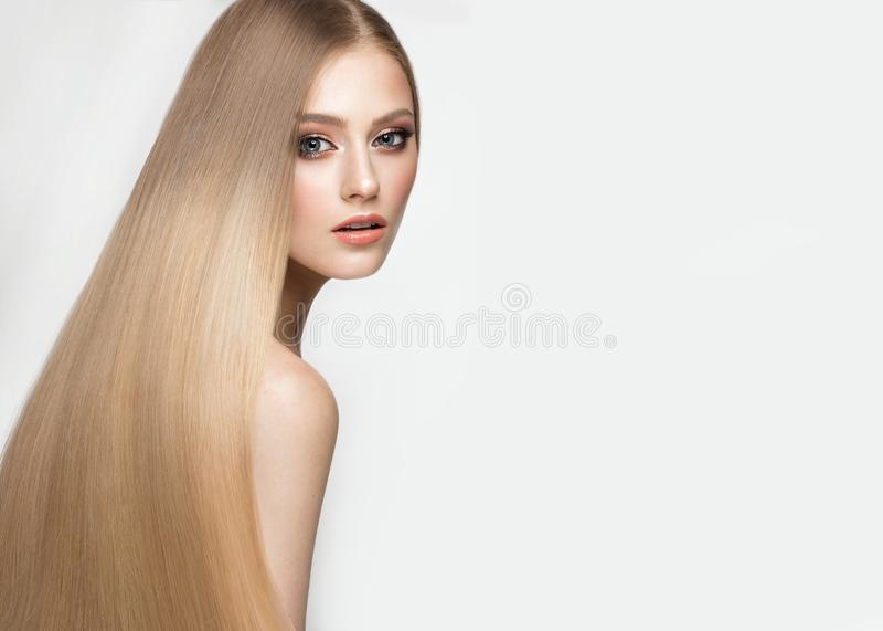 Härlig blond flicka med ett perfekt slätt hår och klassiskt smink Härlig le flicka arkivbilder
