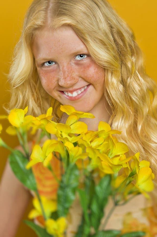 Härlig blond flicka med fräknar som rymmer en bukett av blommor royaltyfri foto