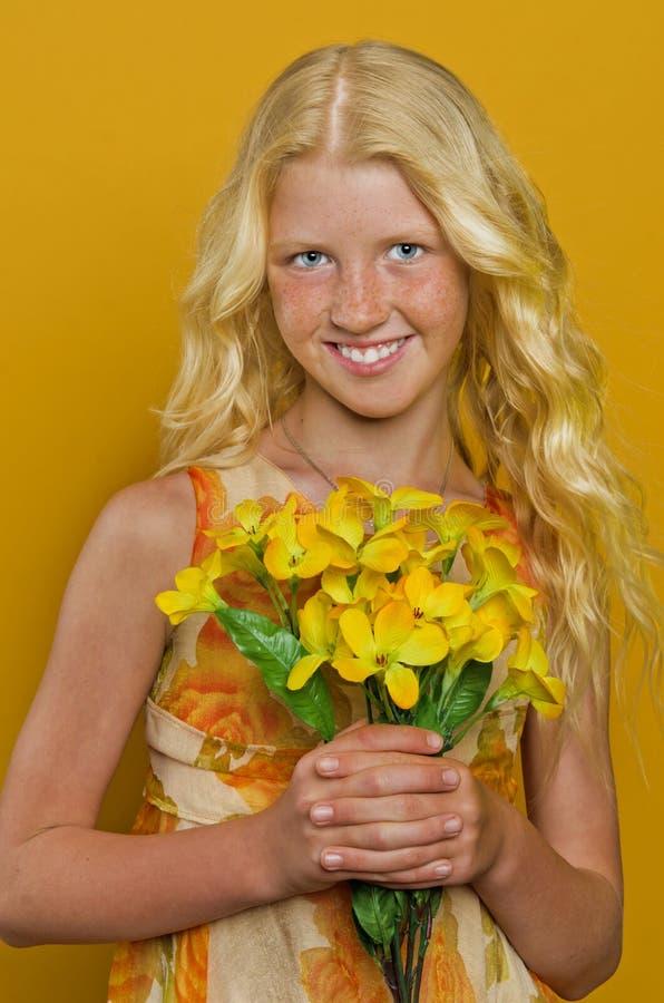 Härlig blond flicka med fräknar som rymmer en bukett av blommor arkivfoton