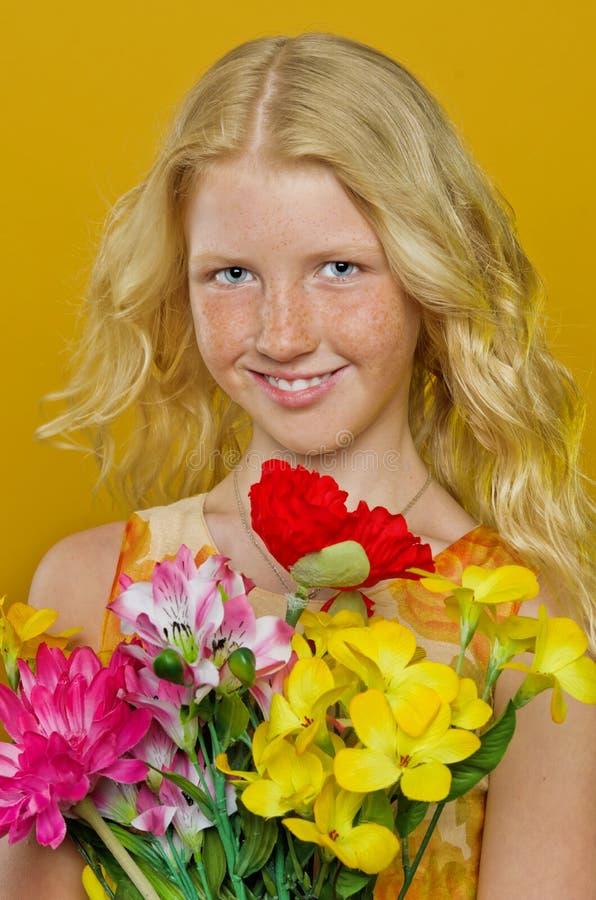 Härlig blond flicka med fräknar som rymmer en bukett av blommor royaltyfri fotografi