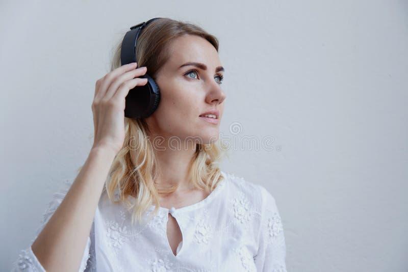 Härlig blond flicka med hörlurar på en ljus bakgrund Hon tycker om att lyssna till musik, att sjunga och att ha gyckel royaltyfria bilder