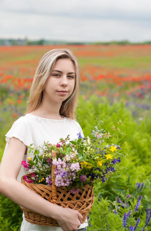 Härlig blond flicka med korgen av vildblommor arkivbild