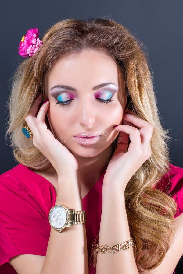 Härlig blond flicka med ljus makeup, långt krullat hår och massiva smycken på grå bakgrund skjutit mode arkivbild