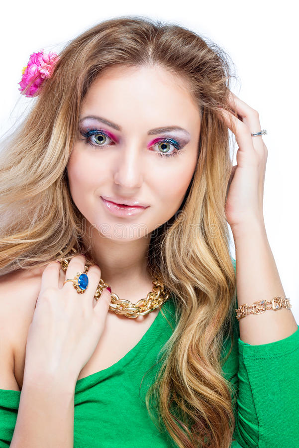 Härlig blond flicka med ljus makeup, långt krullat hår och massiva smycken på vit bakgrund skjutit mode arkivfoton