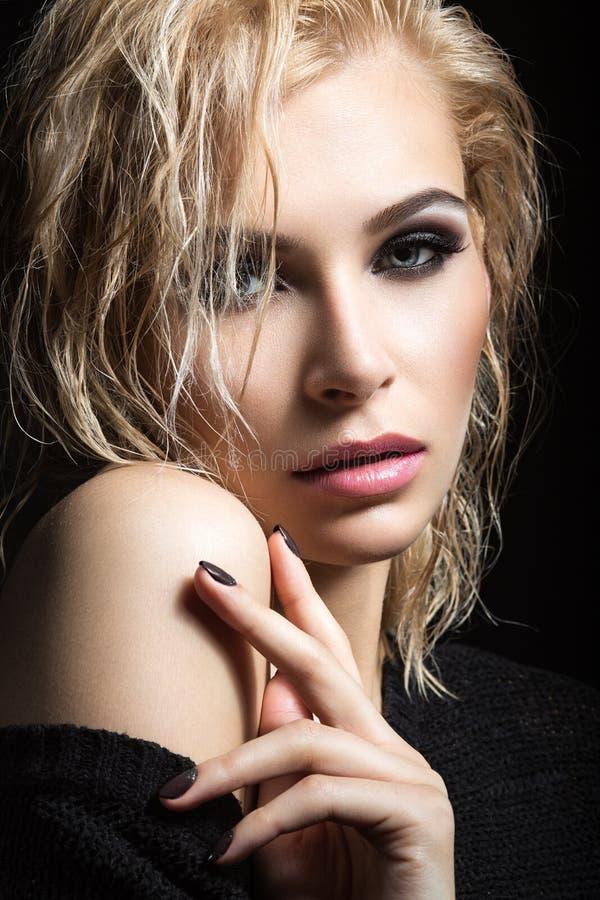 Härlig blond flicka med vått hår, mörk makeup och bleka kanter Härlig le flicka arkivfoton