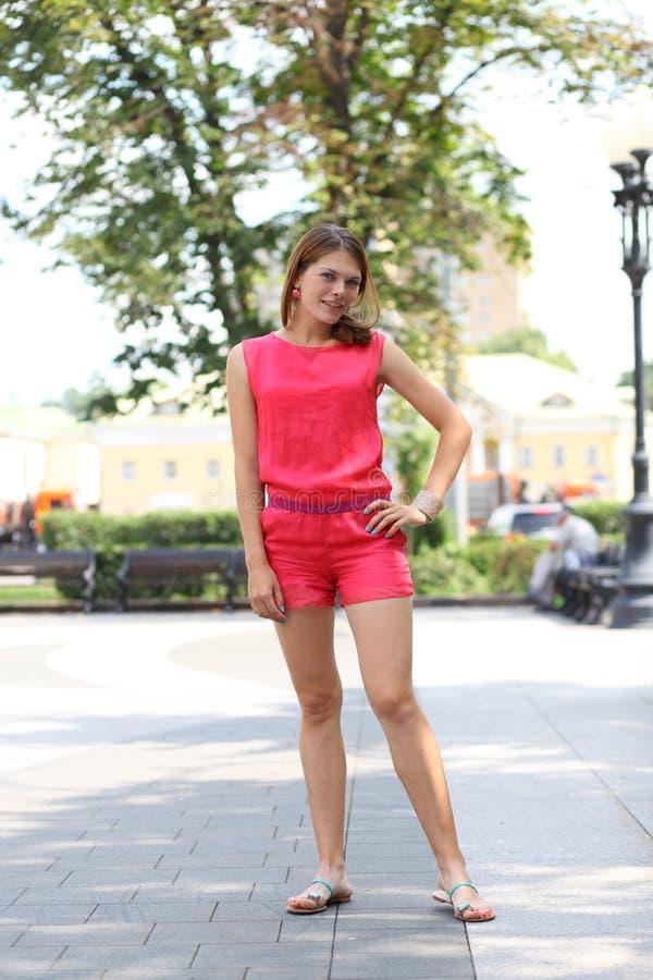Härlig blond flicka på gatan Ung kvinna i röda kortslutningar och en blus arkivfoto