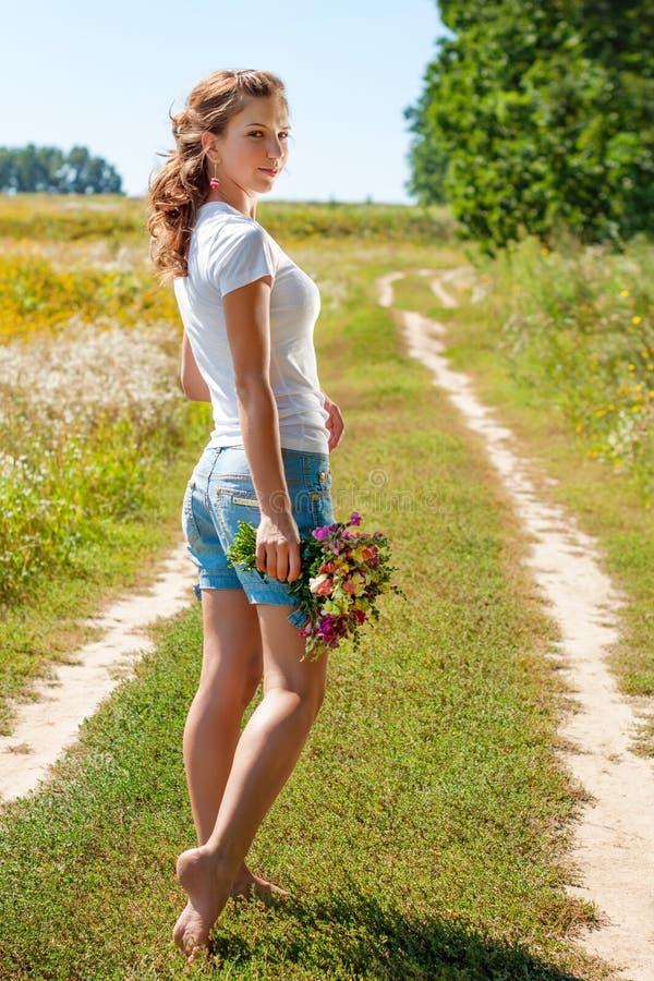 Härlig blond flicka som barfota går på sommarfält med en bukett av lösa blommor fotografering för bildbyråer