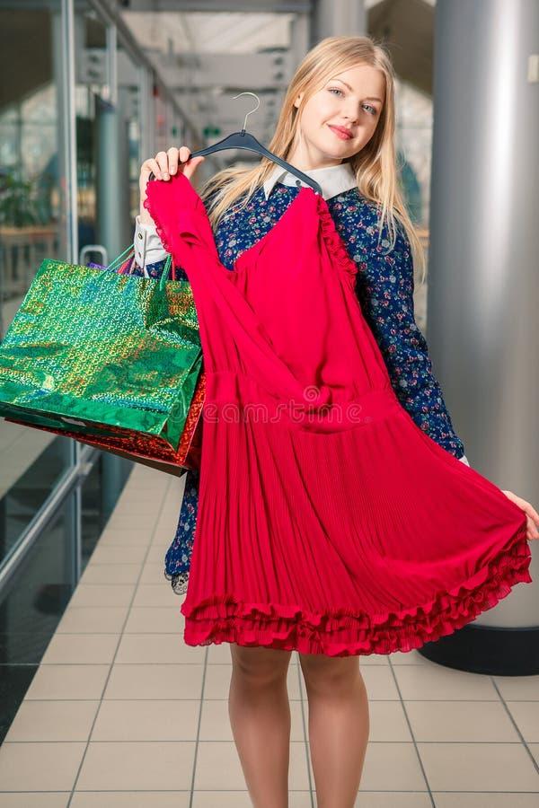 Härlig blond flicka som försöker den nya klänningen på galleria royaltyfri fotografi