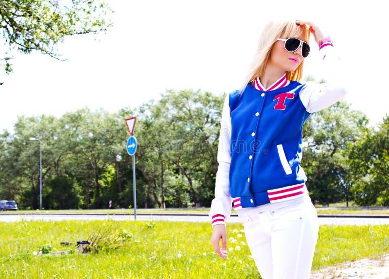 Härlig blond flicka som går på gatan royaltyfri bild