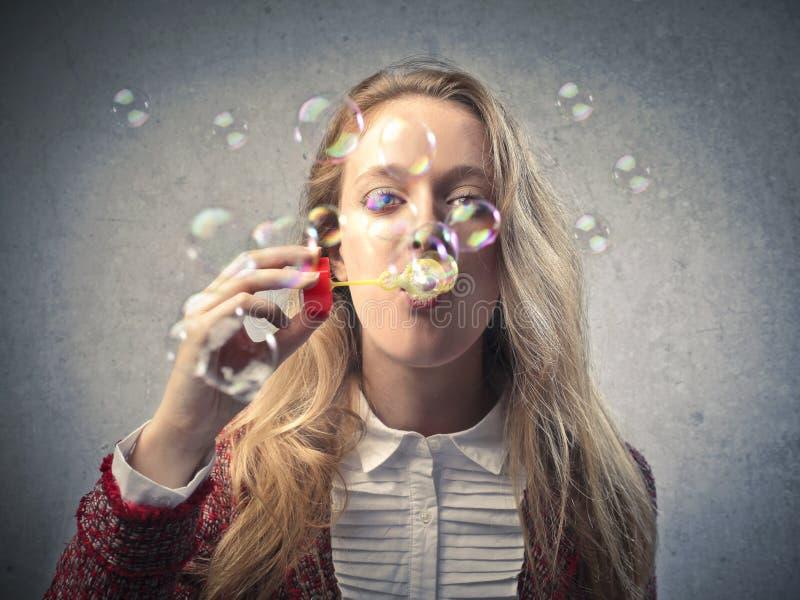 Härlig blond flicka som gör såpbubblor arkivbilder