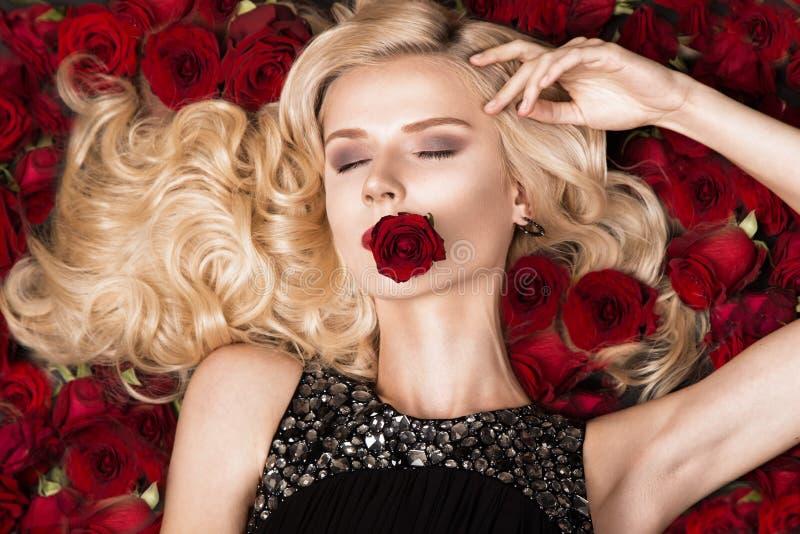 Härlig blond flicka som ligger på bakgrund av rosor Krullning röd läppstift, aftonklänning Härlig le flicka fotografering för bildbyråer