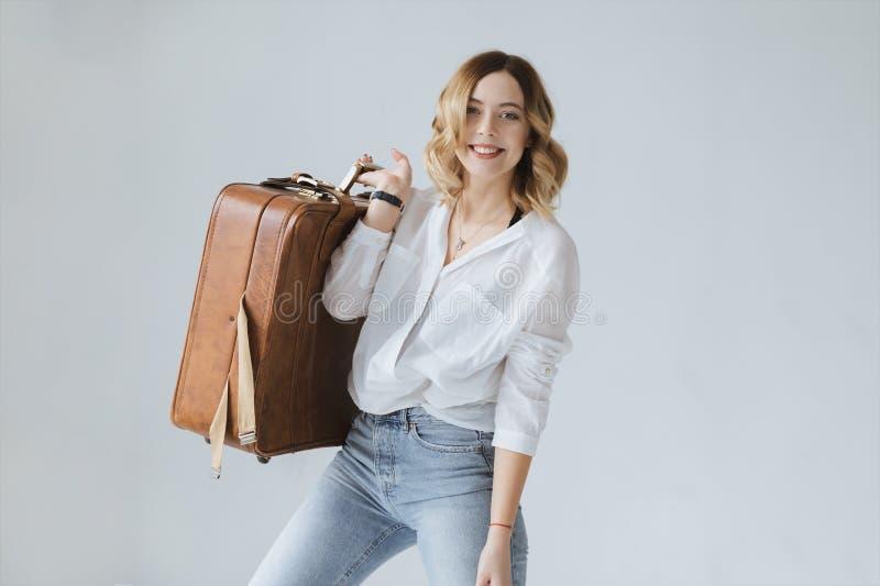 Härlig blond flicka som rymmer en stor resväska royaltyfria bilder