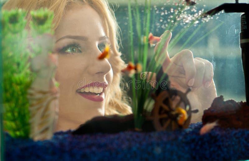 Härlig blond flicka som ser guld- fiskar i akvarium. Attraktiv kvinnlig med ursnyggt leende som beundrar ett stort akvarium royaltyfria bilder
