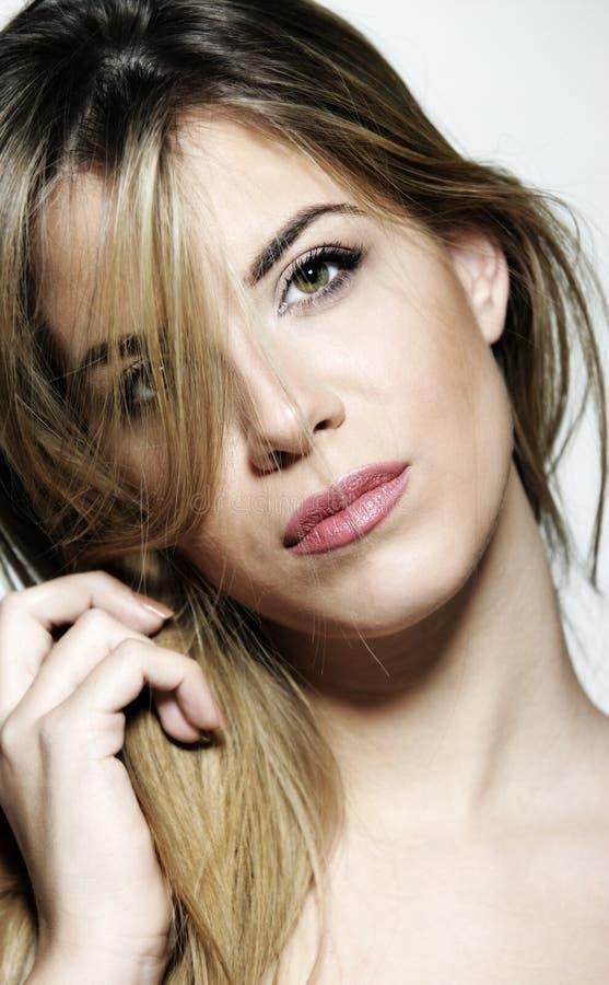 Härlig blond framsida för ung kvinna med gröna gula ögon arkivfoto