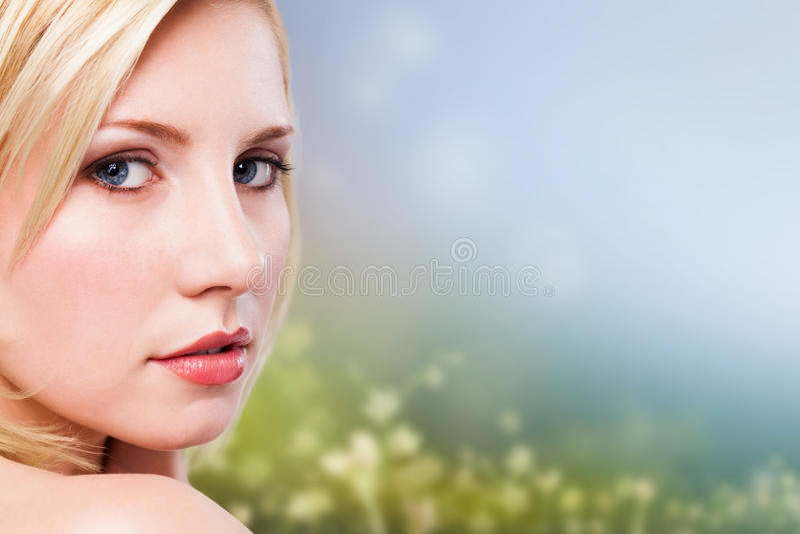 Härlig blond kvinna framme av en vårplats royaltyfri bild