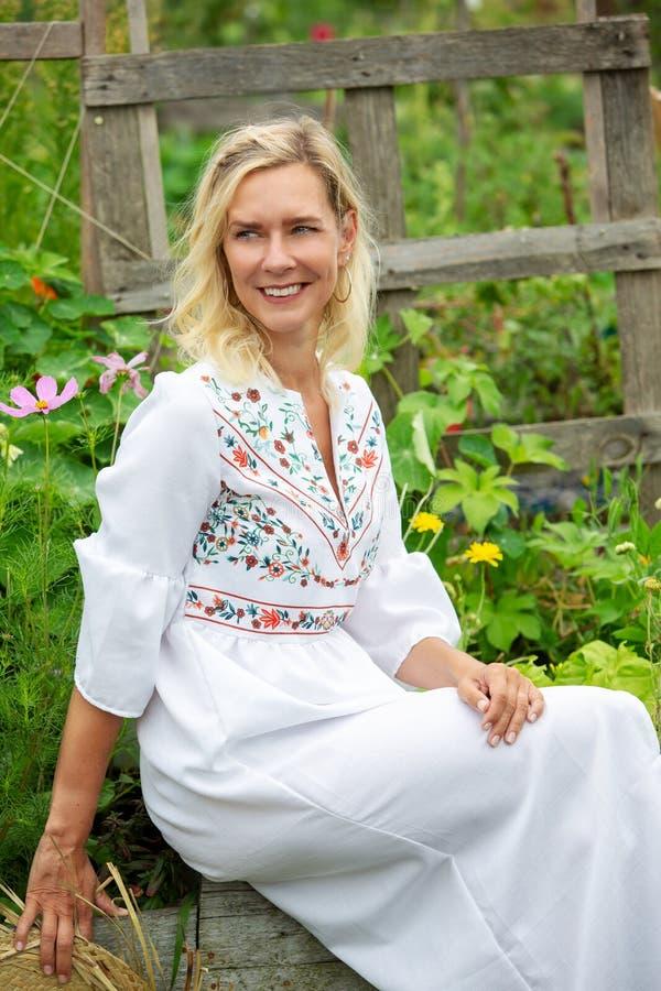 Härlig blond kvinna i den vita klänningen som sitter utanför i trädgård royaltyfri bild