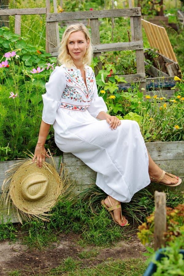 Härlig blond kvinna i den vita klänningen som sitter utanför i trädgård arkivbild