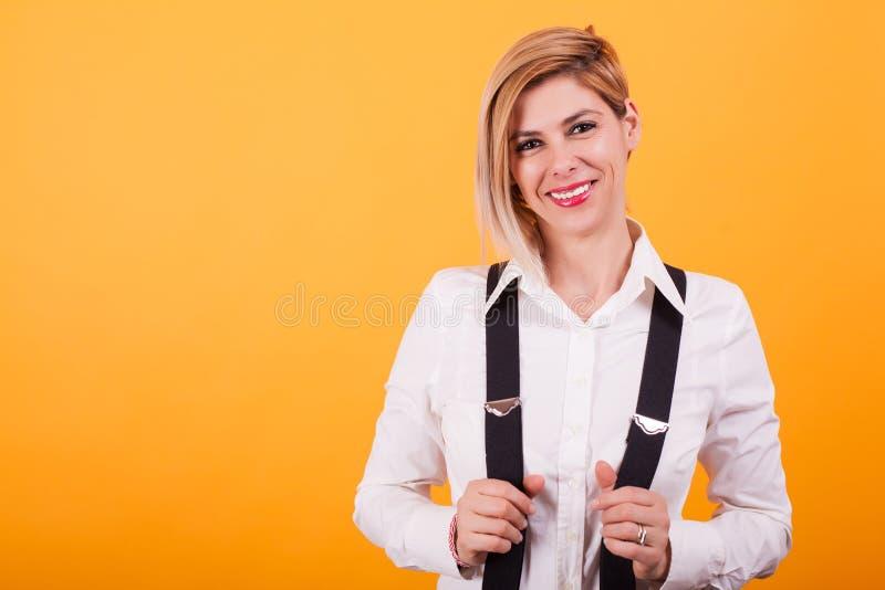 Härlig blond kvinna i den vita t-skjortan som ser kameran över gul bakgrund royaltyfria foton