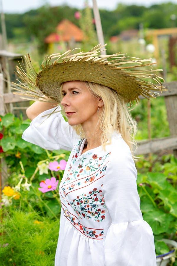 Härlig blond kvinna i det vita klänninganseendet i trädgård royaltyfria foton