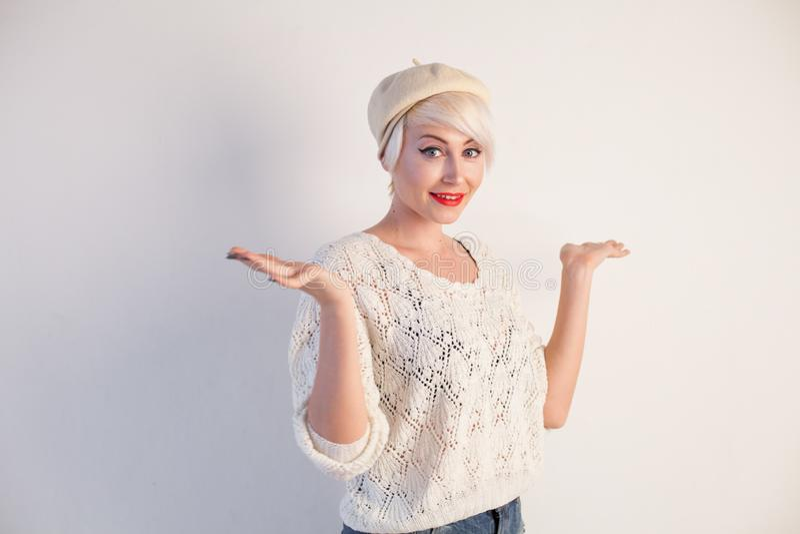 Härlig blond kvinna i en basker och en ljus klänning på en vit bakgrund arkivfoton