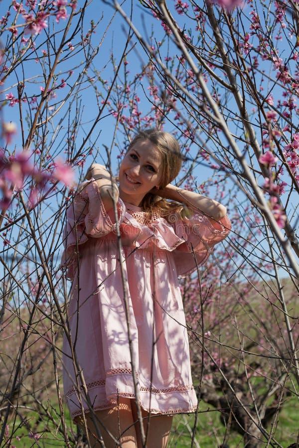 Härlig blond kvinna i en blommig persikaträdgård i vår med rosa blommor fotografering för bildbyråer