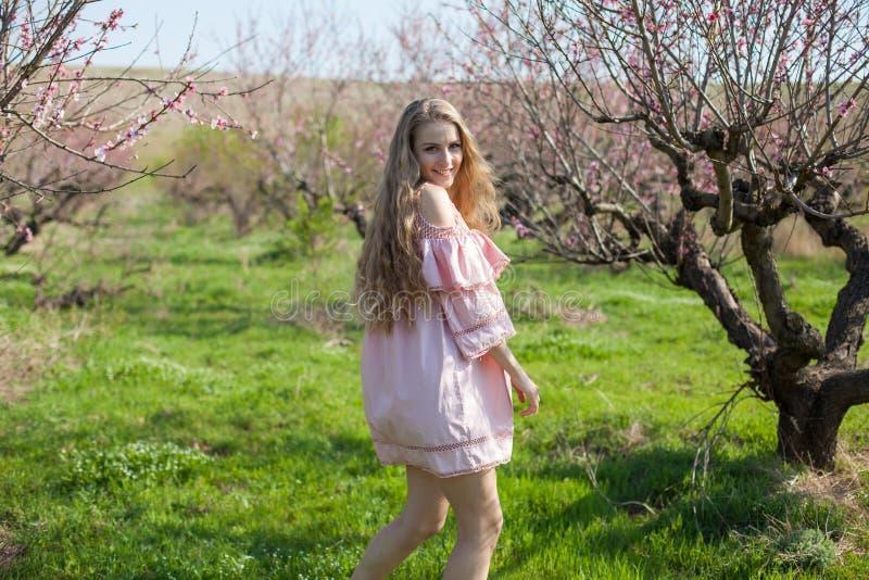 Härlig blond kvinna i en blommig persikaträdgård i vår med rosa blommor royaltyfri fotografi