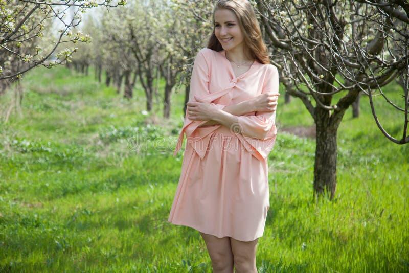 Härlig blond kvinna i en blommig trädgård royaltyfri bild