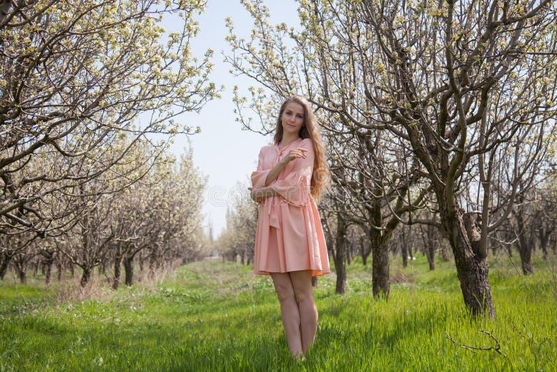Härlig blond kvinna i en blommig trädgård royaltyfria foton
