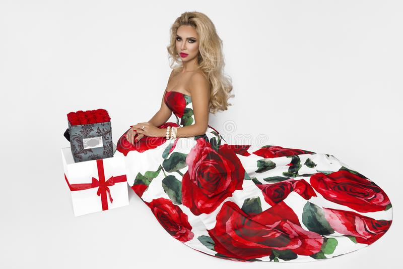 Härlig blond kvinna i en elegant aftonkappa med röda rosor som rymmer en gåva Chrismas tid En modell som poserar i studion royaltyfria bilder