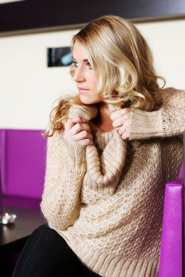 Härlig blond kvinna i en stång eller en kafeteria royaltyfria foton