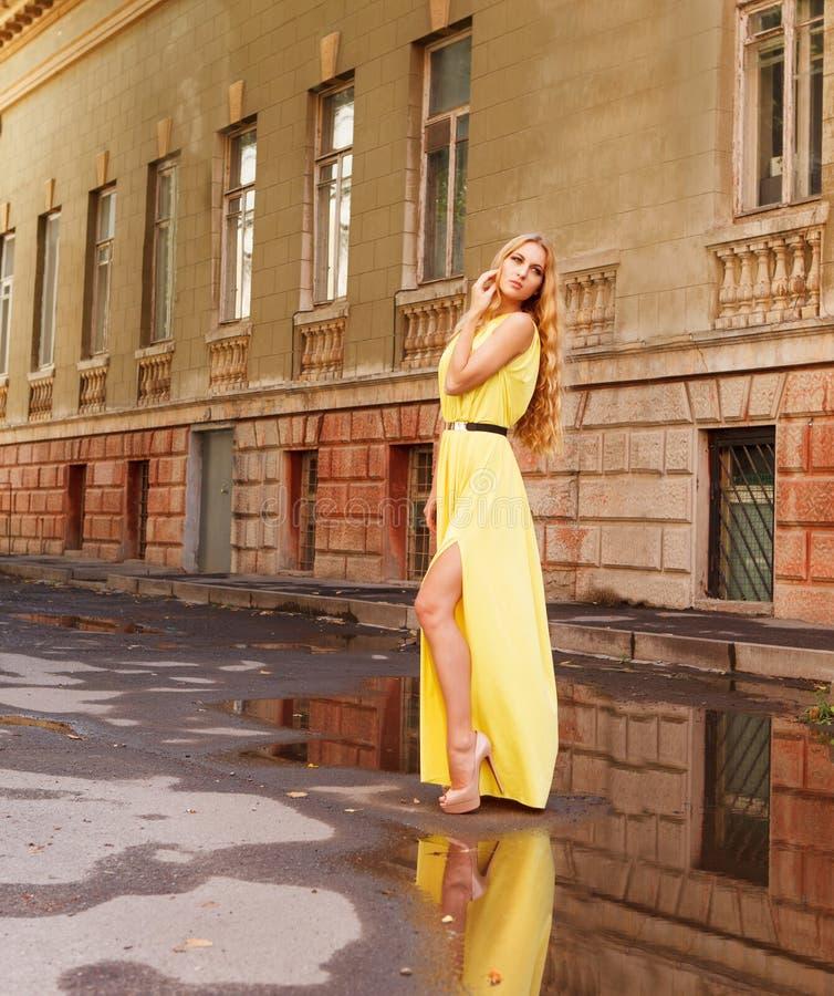 Härlig blond kvinna i lång gul klänning utomhus royaltyfria bilder