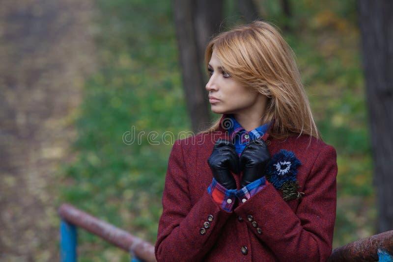 Härlig blond kvinna i omslags- och läderhandskar arkivbild
