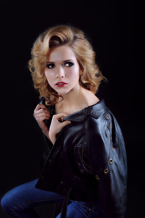 Härlig blond kvinna i svart läderomslag och jeans retro arkivbilder
