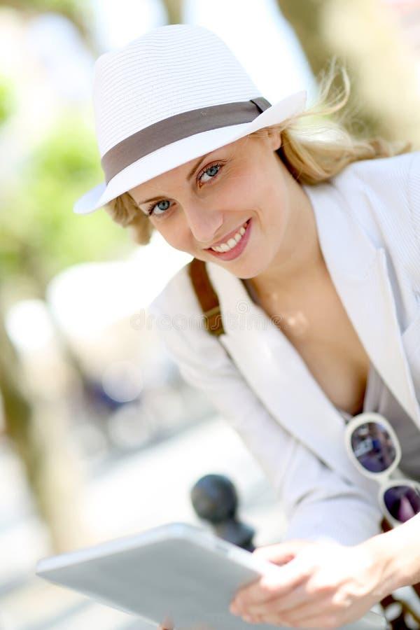 Härlig blond kvinna med den vita hatten genom att använda minnestavlan royaltyfri bild