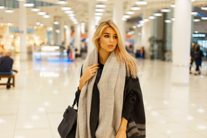 Härlig blond kvinna med en gullig framsida i ett moderiktigt stilfullt arkivfoton