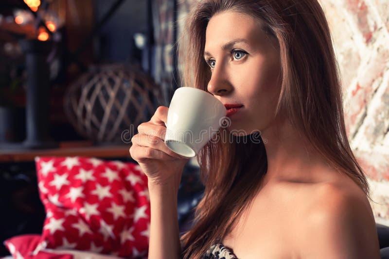 Härlig blond kvinna med en kopp kaffe i en restaurang arkivbild