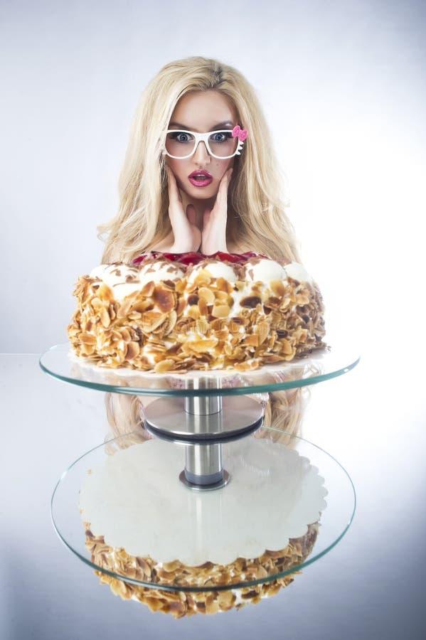 Härlig blond kvinna med en tårta. Söt sexig lady med exponeringsglas arkivbild