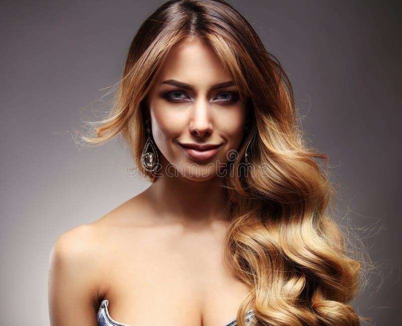 Härlig blond kvinna med länge, sunt, rakt och skinande hår royaltyfri foto