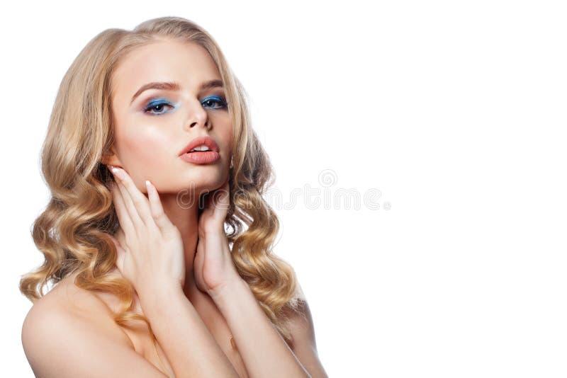 Härlig blond kvinna med långt lockigt hår som isoleras på vit Ursnygg kvinna med makeup och den perfekta frisyren arkivbild