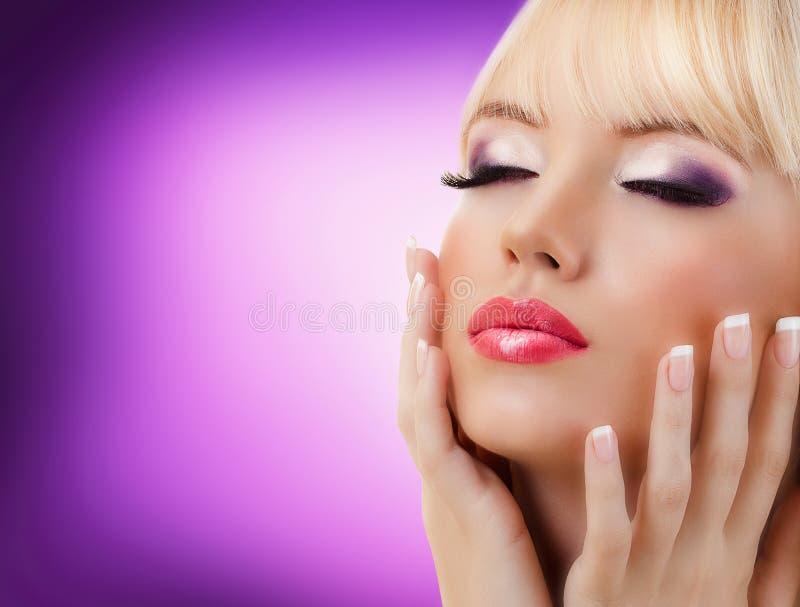 Härlig kvinna med manicure- och lilamakeup arkivbild
