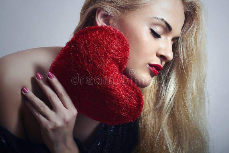 Härlig blond kvinna med röd hjärta. Skönhetflicka. Visa förälskelsesymbolet. Valentindag royaltyfria bilder