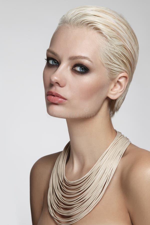 Härlig blond kvinna med rökigt ögonsmink och stilfullt royaltyfri foto