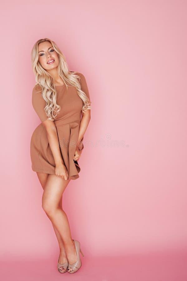 Härlig blond kvinna på rosa färg arkivbilder