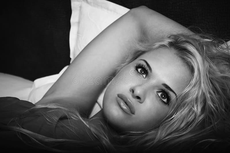 Härlig blond kvinna på sängen royaltyfri bild